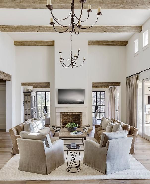 Gorgeous rustic ceiling beams hold iron chandeliers over a beautifully appointed living room boasting a flat panel television mounted above a red brick fireplace as two face to face brown skirted sofas sit separated by a wood and metal coffee table on an ivory herringbone rug while two gray accent chairs are placed flanking a metal end table.