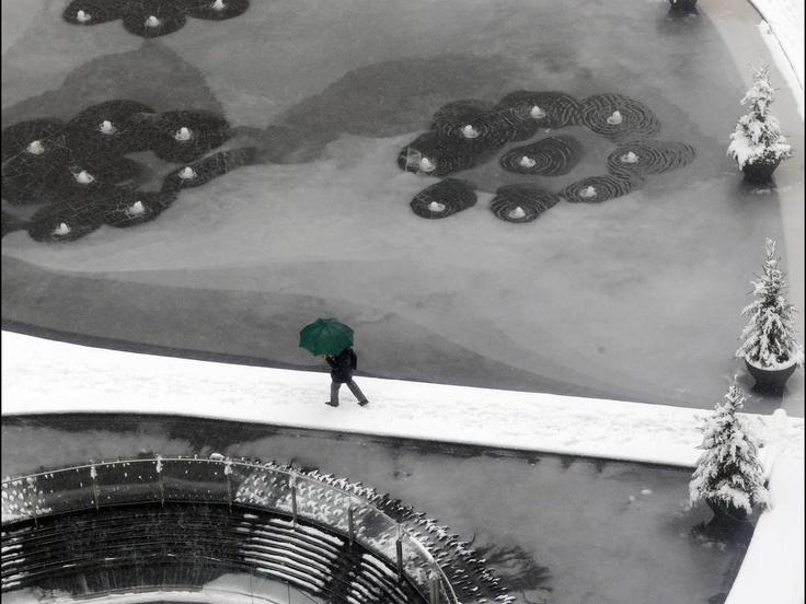 a man walks thru a frozen fountain during a snowfall in milan, italy