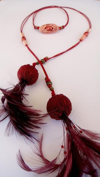 Collar de cuero color rojo con cuentas cerámicas, piezas de zamak, piezas de aluminio y borlas de pasamanería  con cuentas y plumas.
