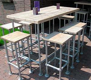 Outside bar and matching stools made from scaffold tubes with planks. Homemade Furniture construction drawings. Barstool and table plans for reclaimed wood and scaffolding tubes. Free construction drawings and assembly instructions to make bars stools and matching tables. Build a barstool with reclaimed scaffolding tubes and boards.