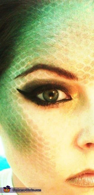 Cateline: I'm wearing the costume. I always try to have costumes that allow for extravagant makeup. I did the scales by stretching fishnet stockings over my face then layering makeup colors....