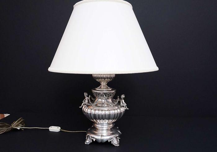 Figuratieve lamp met 2 Cupido Italië beg. 20 c.  Figuratieve lamp met 2 Cupido.In totaal zijn ze gemaakt van zilver 800/1000.Oorsprong-Italië de helft van de 20e eeuw.Zilveren gemarkeerde 800 en zilversmid markeren.Basis diameter 13 cm. totale hoogte met schaduw 50 cmHoogte van zilveren deel 31 cm. lager diameter van lampenkap 40 cm.Het brutogewicht van de lamp (zonder kabel en lampenkap en lamp) is 15 kg.Het is stabiel en zeer solide.Lamp is in zeer goede staat. De kap is nieuw in romige…
