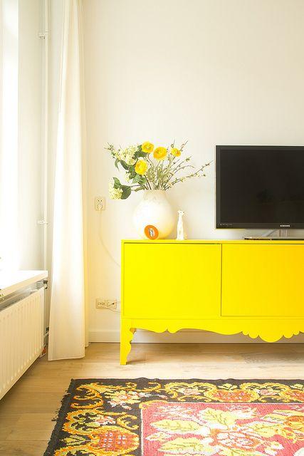 Se você tem preferência por cores neutras na decoração, mas sabe que muito neutro pode deixar o ambiente cansativo, a ideia é usar pontos de cor. Pode ser em almofadas, tapetes como no caso e até em algum móvel.