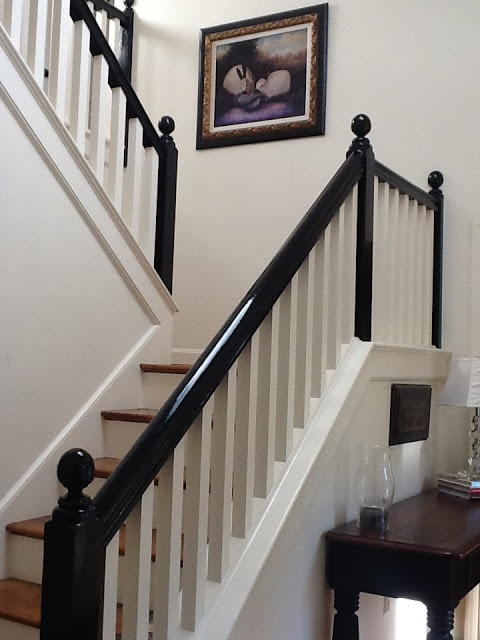 White entryway with stairway with black banister.