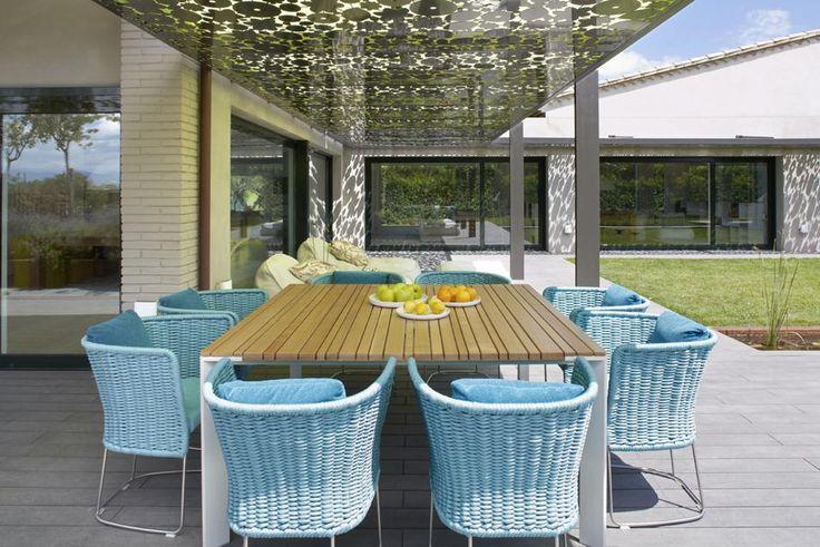 PRANZI ALL'APERTO Il tavolo, arredato con poltrone in vimini colorate, diventa ideale per pranzi all'aperto. Un pergolato in acciaio con foglie stilizzate sulla pensilina di copertura genera dinamici giochi d'ombra.