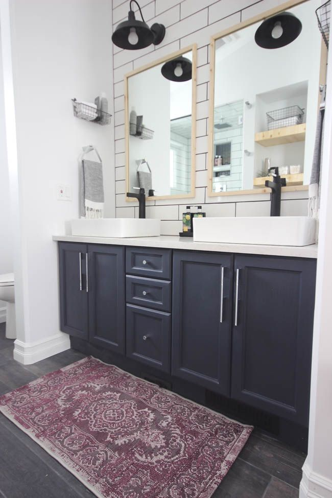 A beautiful modern bathroom renovation with chrome and matte black faucets, sleek modern fixtures and natural wood accents. Beautiful transformation! Subway tile with black grout, wood grain tile, chandelier above tub, matte black faucet, matte black lighting, maroon rug, purple rug, rectangular vessel sinks, natural wood accents, industrial chic