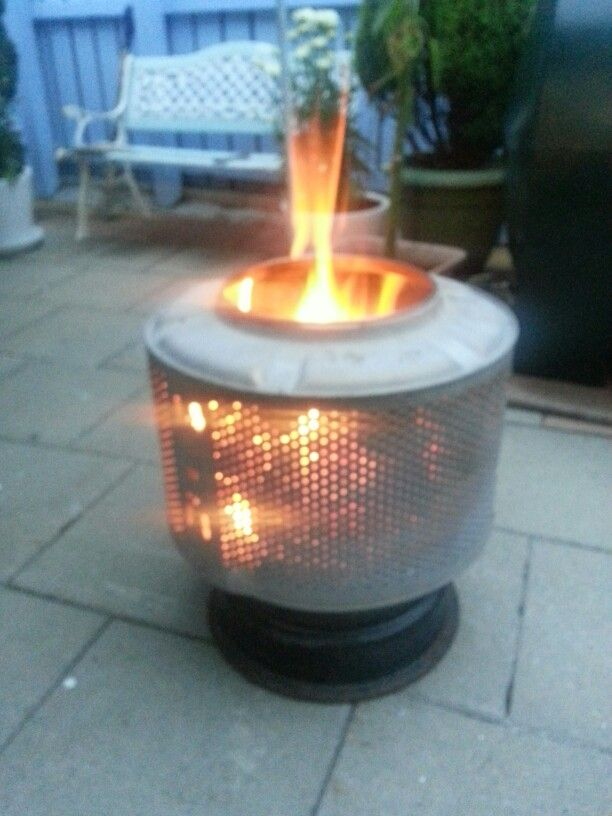 Tyre rim & an old washing machine drum.  Perfect outdoor fire pit!