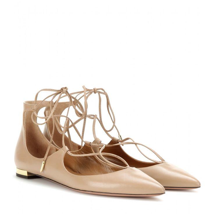 """Mit ihrer spitzen Silhouette mit filigraner Schnürung sind die """"Christy Flat""""-Ballerinas von Aquazzura superfeminin. Der goldfarbene Mini-Absatz verleiht Extra-Eleganz. Unkomplizierter Chic für tagsüber, aber auch abends eine adäquate Alternative zu Heels."""