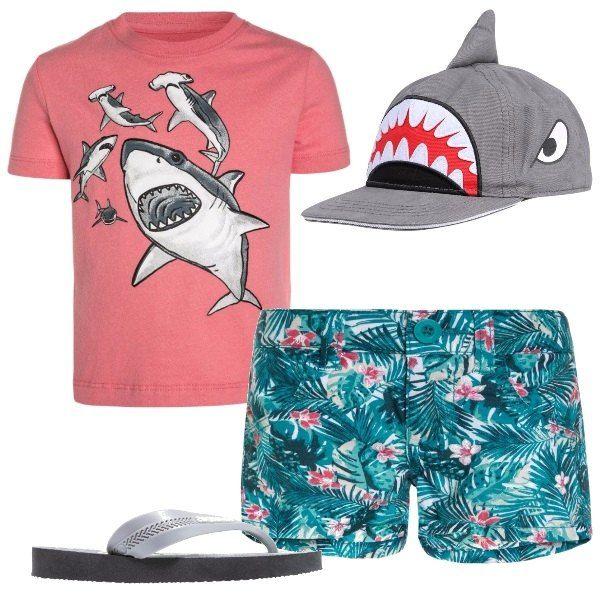 Maglietta maniche corte con stampa di squali, pantaloncini corti fantasia hawaiana, infradito grigi e simpatico berrettino con visiera con la pinna di uno squalo.