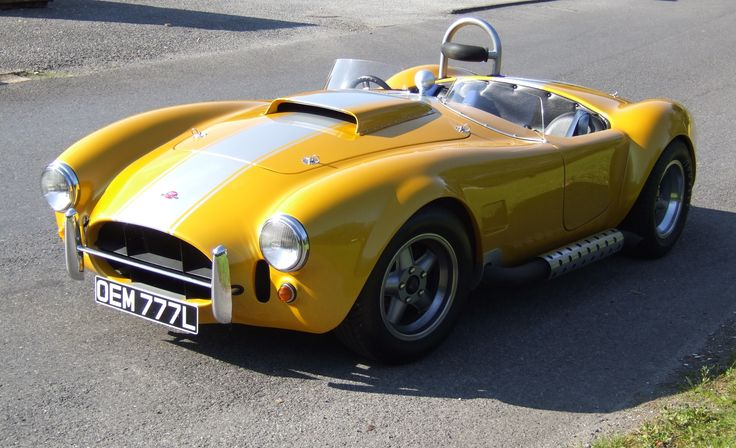 Magnum 427 AC Shelby Cobra replica in yellow, posh yellow. With a silver stripe. And it's got wheels on and chairs in it. Oh, and an engine and stuff too.
