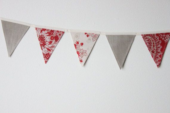 Fabric bunting can be used over and over again! Party decorations, nursery or kid's room decor, over a doorway or around a window, the options are endless! This bunting is made up of 3 different fabrics, a red and grey floral with a white background, a red paisley, and a solid grey. #theevergreencollective