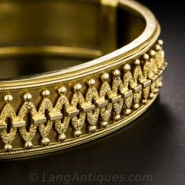 From 19th Century Victorian England comes this light and lovely hinged bangle bracelet, elegantly crafted in 15K yellow gold and overlaid with an intriguing, textured geometric design. 9/16th inch wide, with a few minor dents and crinkles here and there.