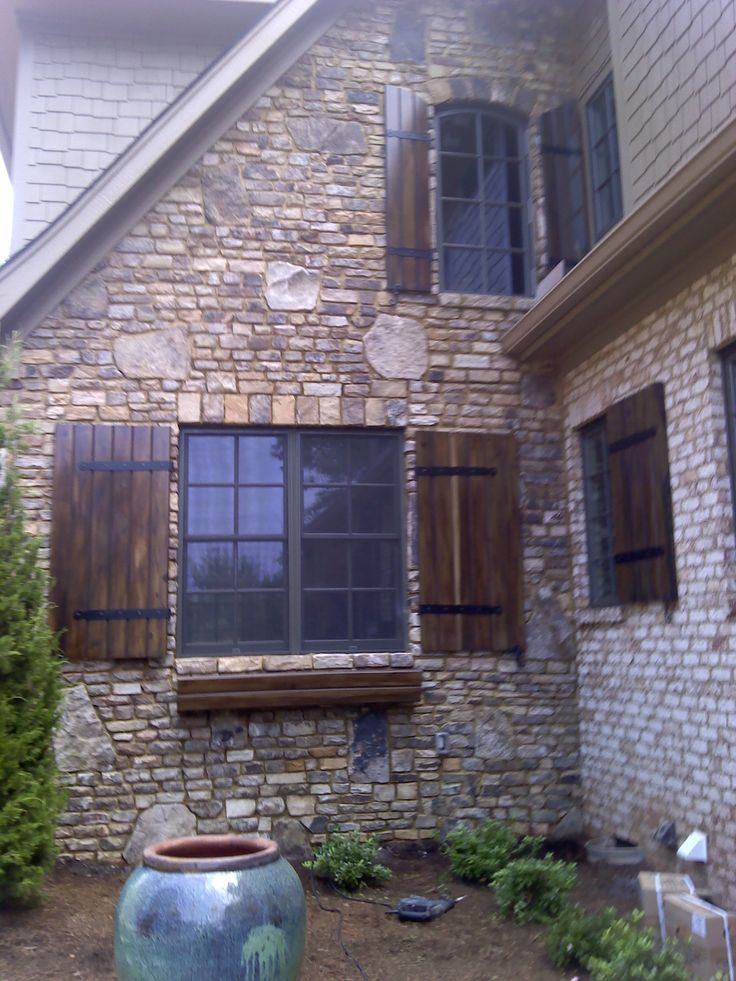 nothing more beautiful than custom dark stained wood shutters on a brick and stone home persianas de
