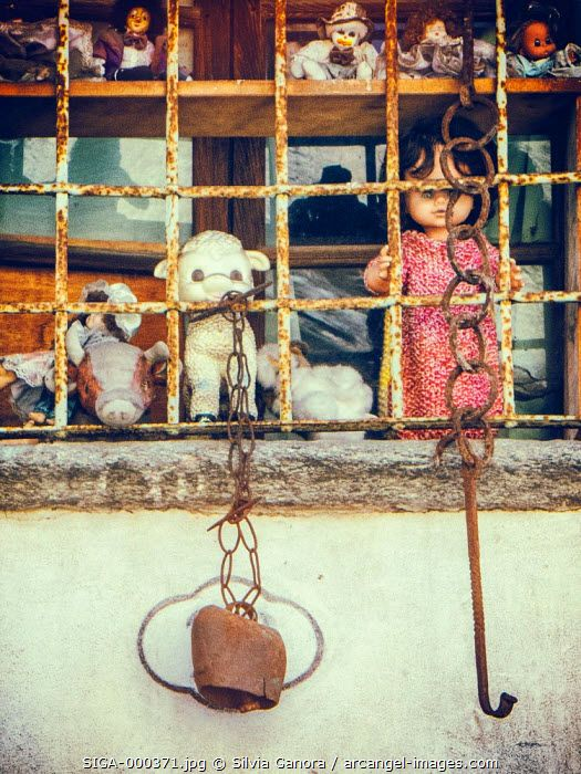 Spooky puppets, dolls and toys grouped on a window sill and protected by a rusty grate. - ©Silvia Ganora Photography - All Rights Reserved  #bookcovers #dolls #creepy #puppets