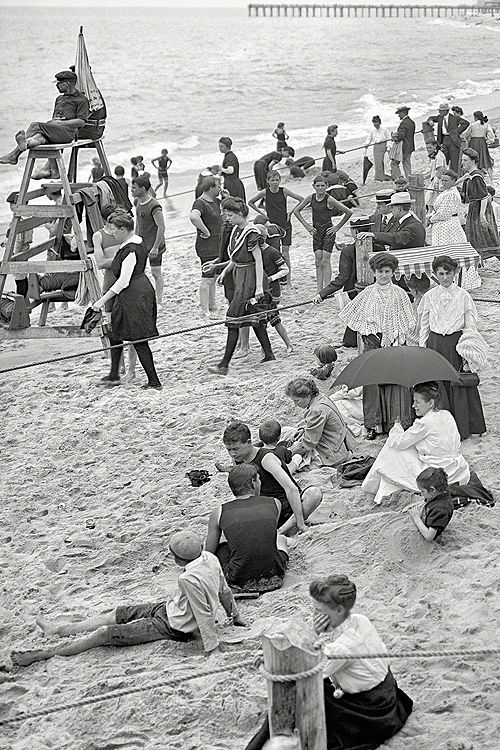 American Gilded Age era view of the Jersey Shore - New Jersey, c.1905. Photograph include; sunbathers on the sand, lifeguard on stand, modest beach swimming suits, ladies, gentlemen and childen in full street attire, a lady with an umbrella for shade from the sun, and wool bathing suits. ~ {cwl} ~ (Image: librar-y tumblr)