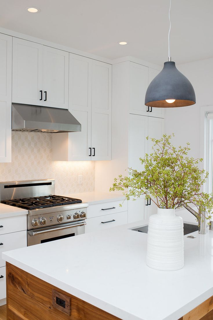 Fresh white kitchen with warm wood wrapped island, black cabinet pulls and Dwell patterns Heath tile backsplash . Photo 2 of Chenery Street Remodel modern home