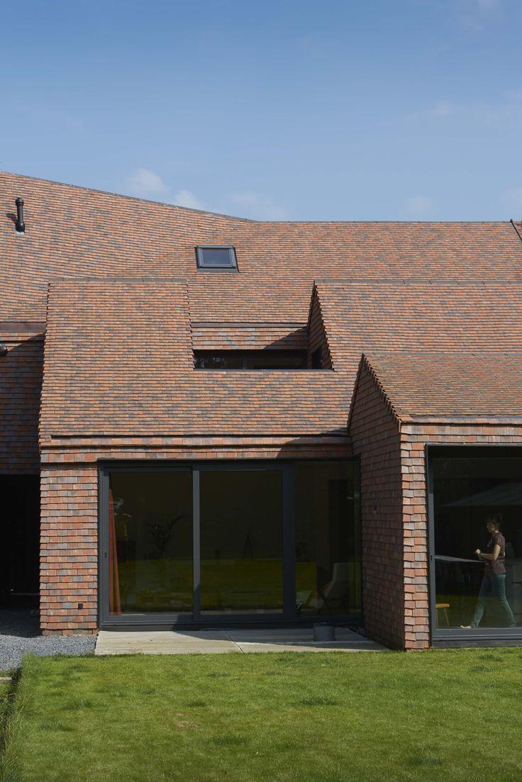Maison monobloc (Acht en half architectuur, Pieter Uyttenhove, Evergem). Pour accentuer encore davantage le toit, les architectes ont cherché un matériau permettant de parachever tant la façade que le toit. Existe-t-il dans ce cas un matériau qui crée un lien plus solide avec un toit qu'une… tuile de toit. Avec leurs teintes de terre, les tuiles plates utilisées – un mélange Vert de Lichen, Rouge de Mars et Noir de Vigne – contrastent joliment avec les menuiseries noires et les détails…