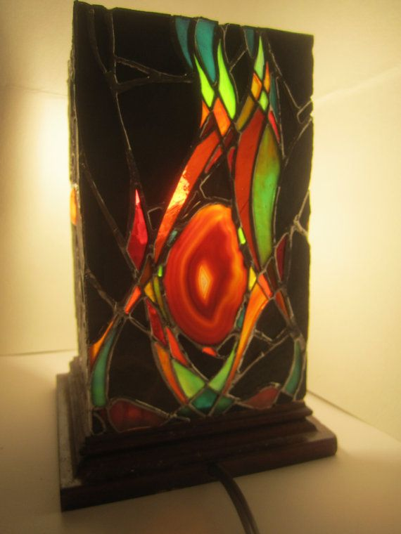 This is a hand-made stained glass and slate stone lantern, with two sides containing a piece of agate (geode). Slate was carefully chipped and shaped to fit together and assembled with the stained glass pieces. The dimensions of each side are approximately 5 x 8 inches and were assembled using the copper-foil method. The lantern sits on a stained solid maple wood base and comes wired with a 6 ft. cord.