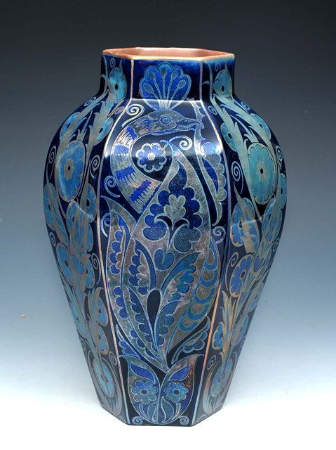 "William De Morgan (British, 1839-1917) An hexagonal tapering vase, painted by Fred Passenger, with panels of stylised peacocks and flowering foliage, in blue and silver lustre, painted 'FP' monogram to the base, 10"" high."