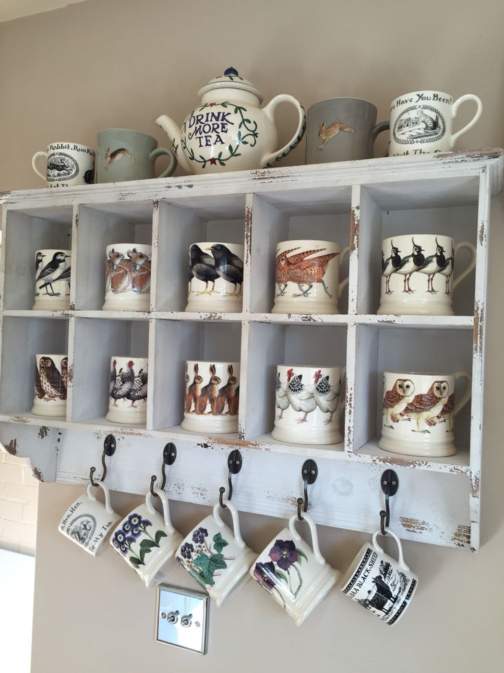 Assorted Emma Bridgewater mugs and Drink More Tea teapot. Pigeon hole shelving.