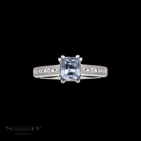 A unique silvery pastel blue natural unheated sapphire is double claw set in white gold and beautifully enhanced by a double milgrain detailed band. Set with French cut diamonds, that really add the finishing vintage touch. All handmade the traditional way.