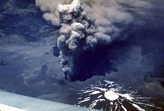 Four days after the start of an eruption from Lonquimay volcano on December 25, 1988, a vigorous ash column rises above a vent on the NE flank. Winds distribute the ash column to the SE. Heavy ashfall from the eruption, which lasted over a year, caused severe economic disruption.  The dark area extending to the left from the eruptive vent, which formed along a fissure system trending NE from the summit, is a