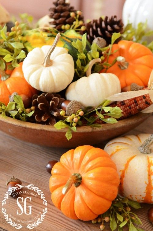 Fall centerpiece - wooden bowl filled with pumpkins, pinecones and greenery.