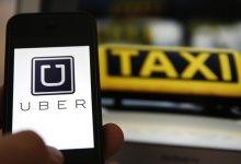 Uma imagem de ilustração mostra o logotipo de car-sharing app serviço Uber em um smartphone ao lado da imagem de um sinal do táxi oficial alemão em Frankfurt, 15 de setembro de 2014. REUTERS / Kai Pfaffenbach