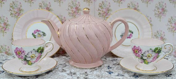 Vintage bone china tea set for two, made by English china company Royal Grafton and well known teapot maker Sadler, likely manufacture date 1960s. The set consists of full size teapot, tea cups, saucers and tea plates- two of each and a milk jug and sugar bowl. The Royal Grafton china is predominantly pale pink with a picture of flowers on the outside of the cups, jug and bowl and in the centre of the plates and saucers. The interior of the cups is pink. The china is further enhanced with…