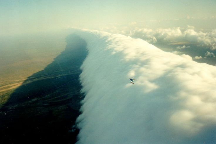 """Roll cloud hang glider, Queensland, Australia - A variety of arcus cloud, tube-shaped rollers are completely detached from the cloud bodies around them and appear to roll as they move low across the sky. Here, Red Bull athlete Jonny Durand hang glides Queensland's """"Morning Glory."""""""