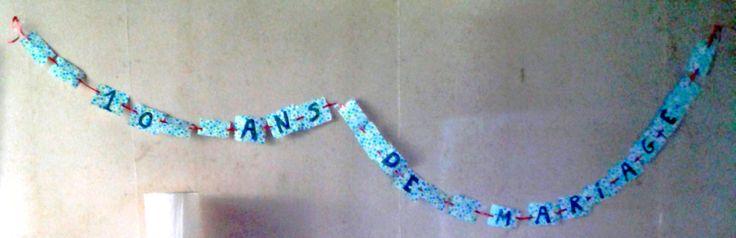 """Guirlande - """"10 ans de mariage"""" - ruban bolduc rouge et rectangles découpés dans du papier décoré HEMA"""