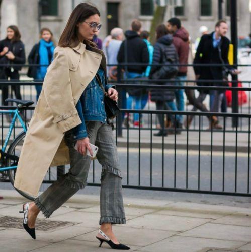 Utiliza una gabardina con una chamarra de mezclilla, pantalón de cuadros y zapatos de tacón.
