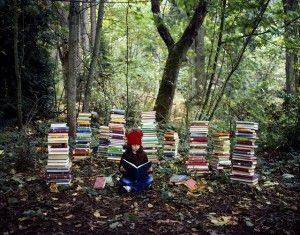 A photo of a child reading books in the woods used in the ongoing peak oil story on Transition Voice, the peak oil magazine, http://transiti...