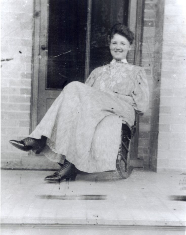 c1905 - Woman sitting on wooden rocking chair on front porch. Wooden hammock to left. Note grape-vine lace pattern on woman's dress, and her lace-up boots.Glass negative image.