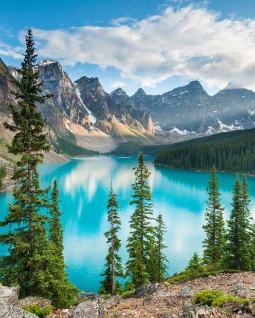 Puede ver un lago, el agua es muy azul, puede ver tambien arboles y montanas con nieve En la parte superior de la misma. Este foto es muy hermosa