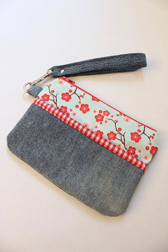Wristlet available on ETSY. Worn jeans are given new life when combined with printed fabrics in this handy zipper wristlet. Great for use as a small purse. Just the right size for your phone, cards and money. It can also fit inside a larger bag and used to contain cosmetics, craft supplies, you name it!  Bag is constructed using upcycled denim jeans and highlighted with a bright turquoise fabric with a red cherry blossom print with a mini red and white check trim and lining and features a…