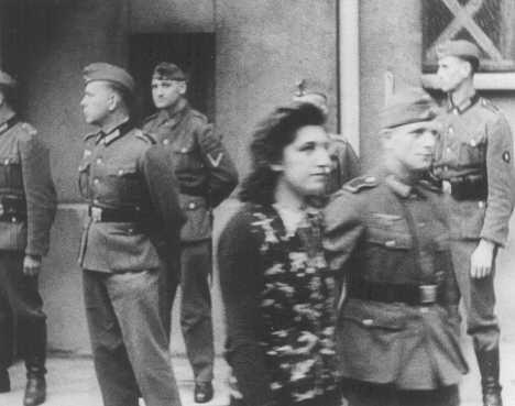 Foto de Simone Schloss, judia que integrava a resistência francesa contra os nazistas, escoltada por um soldado após sua condenação por um tribunal militar alemão em Paris. Ela foi executada no dia 2 de julho de 1942. Paris, França, 14 de abril de 1942.