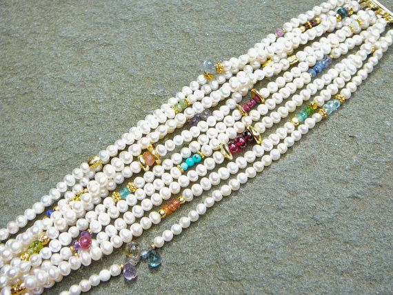 The Marguerite: From the Greek name but really the original Oriental word for pearl, alluding to its beauty and brightness. Ten strands of off white, 4mm freshwater pearls are accented with a panoply of precious and semi-precious gemstones; ruby, emerald, sapphire beads and briolettes, turquoise, lapis, opal, red spinel, garnet...really too many to mention. The gemstones are framed with a variety of vermeil beads. A new take on a classic! Each Marguerite will be slightly different based on…