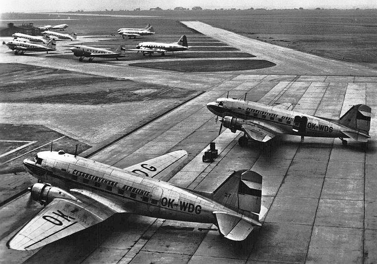 Po válce začalo ruzyňské letiště opět sloužit civilní dopravě. Pohled z první poloviny padesátých let na stání letadel na letišti. Vepředu jsou dvě dakoty, ve vzdálenějším chumlu jsou vlevo další tři dakoty, vpravo tři Iljušiny Il-12 a uprostřed je Lisunov Li-2. Za budovami stojí dvě letadla neidentifikovatelných typů.