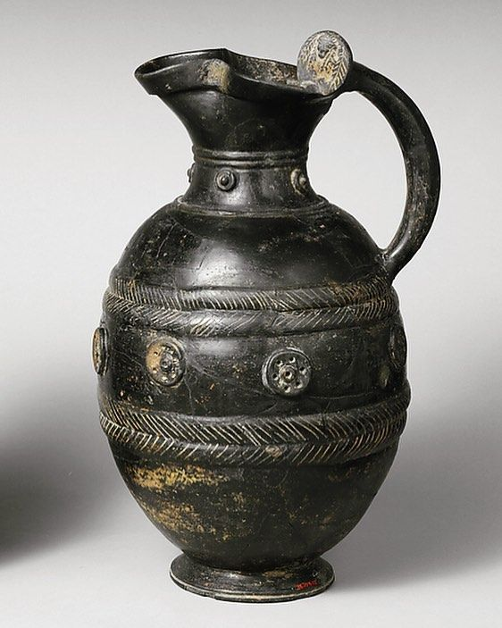 """Etruscan Terracotta trefoil oinochoe (jug) in the @metmuseum. ca. 550 B.C. Terracotta; bucchero pesante """"Bucchero (Italian pronunciation: [bukkero]) is a class of ceramics produced in central Italy by the region's pre-Roman Etruscan population. This Italian word is derived from the Latin poculum, a drinking-vessel, perhaps through the Spanish búcaro, or the Portuguese púcaro."""