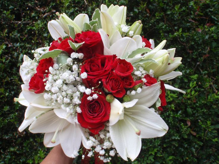 Stunning bright red rose (Red Eagle) and lily  bridal bouquet with gypsophila