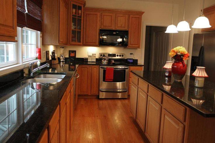 The kitchen features oak cabinets, dark granite counters, and oak floors.
