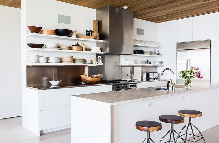 "The open plan kitchen perfectly blends organic and modern styles with bold architectural lines and soft hues. See the full home tour here ""Inside the Breezy Palm Beach Home of Kelly Klein"" on the One Kings Lane Style Guide!"