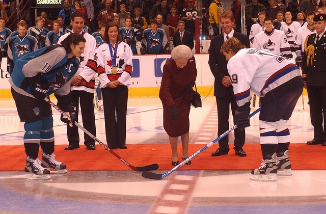 Great Moment: Queen Elizabeth II, with Wayne Gretzky by her side, drops the puck at the Vancouver Canucks –San Jose Sharks hockey game during her Golden Jubilee tour of Canada. Vancouver, British Columbia. October 7, 2002. [Department of Canadian Heritage]