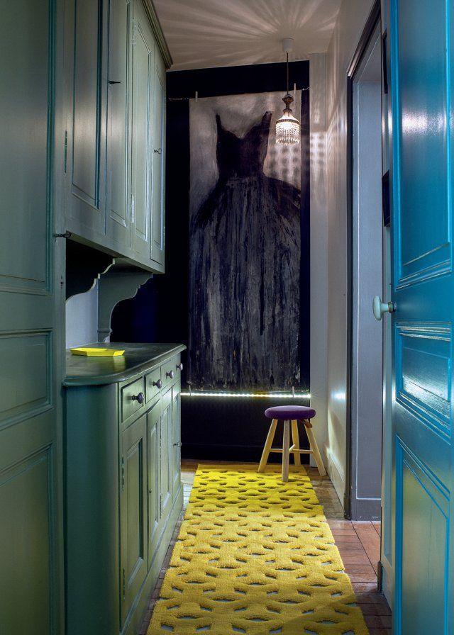 Dans l'appartement de l'architecte d'intérieur Delphine Estour, on accède aux chambres par l'arrière cuisine qui fait office de couloir. Entre le meuble d'origine qui a été peint en vert kaki, la porte bleue et le tapis jaune, ce couloir ne manque pas de couleurs.