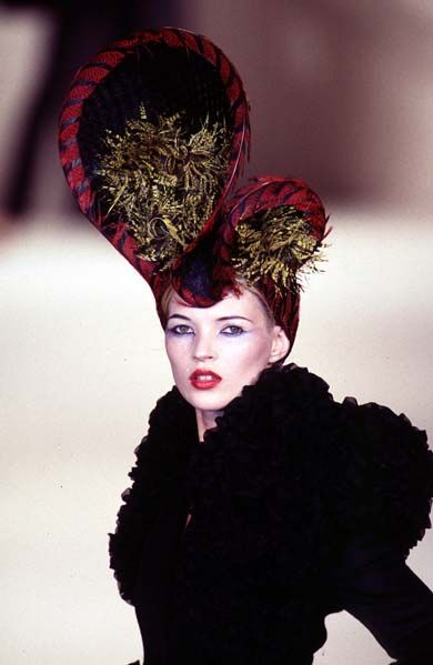 Kate Moss wearing a Philip Treacy fascinator with cherries, berries and large striped bow - Fall/Winter 1996.
