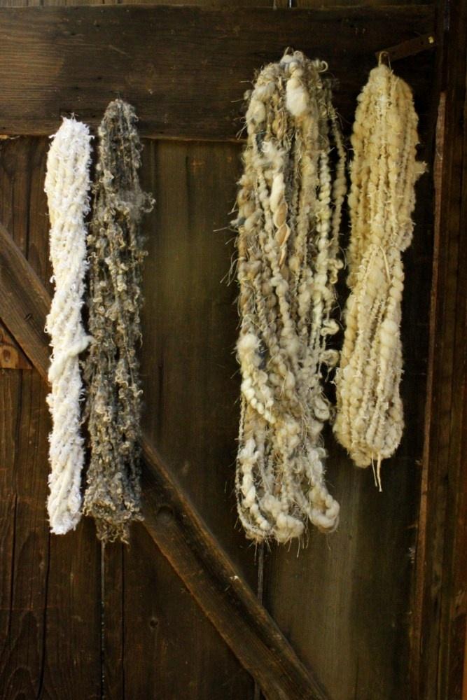 My yarns hang on the Old Barn door (pluckyfluff studio) with Melissa Nasby's yarn