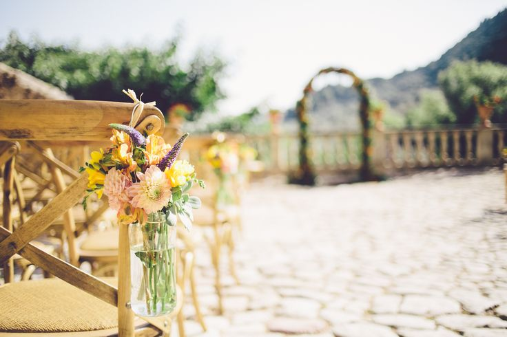 Hanging jars of flowers on the ceremony chairs to add an extra floral detail Photograph by Violeta Minnick Photography
