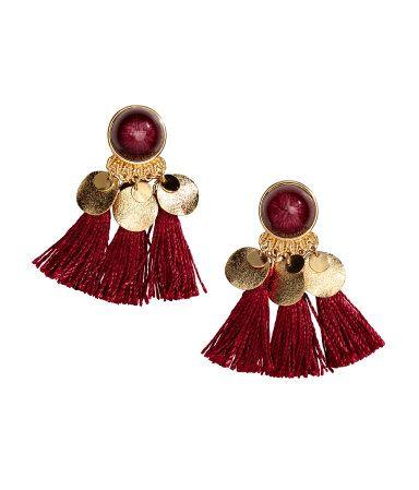 Weinrot. Ohrhänger mit Plastikperle, runden Metallanhängern und Ziertroddeln. Länge 6,5 cm.