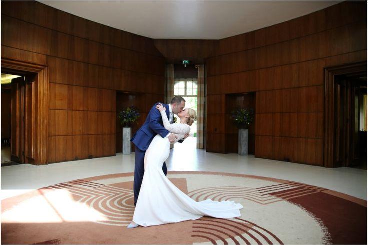 dramatic romantic kiss at art deco hall Eltham Palace London wedding